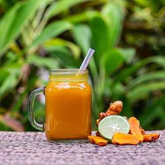 Energietonische drank met kurkuma, gember, citroen en honing in glazen mok, natuurachtergrond, close-up