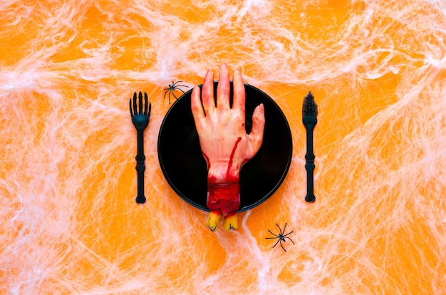 Eng halloween-etentjeconcept met valse scherpe hand op zwarte plaat, mes en vork met spin en spinnenweb op oranje achtergrond.