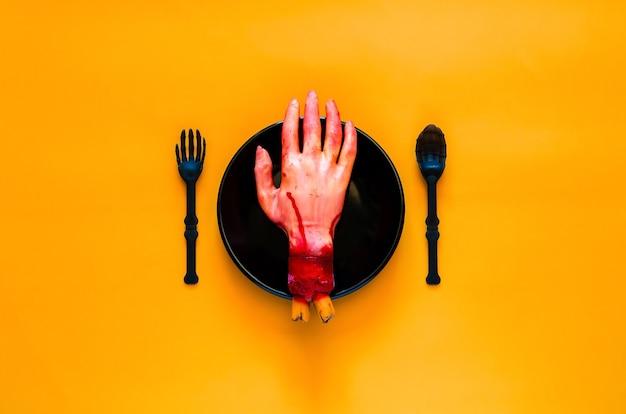 Eng halloween-etentjeconcept met valse scherpe hand op zwarte plaat, vork en lepel en oranje achtergrond.
