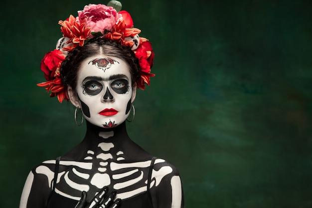 Eng. jong meisje zoals santa muerte saint dood of suikerschedel met lichte make-up. portret geïsoleerd op donkere groene studio achtergrond met copyspace. het vieren van halloween of dag van de doden.