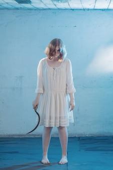 Eng meisje in witte jurk uit horrorfilm op kamer