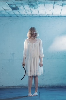 Eng meisje in witte jurk van horrorfilm in de kamer