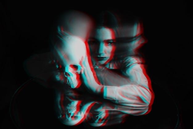 Eng wazig portret van een vrouwelijke heks met een schedel in haar handen op een zwarte achtergrond. zwart-wit met 3d glitch virtual reality-effect