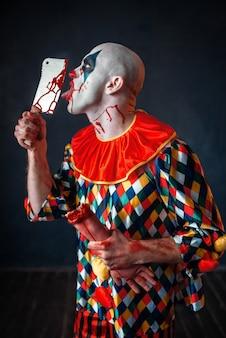 Enge bloedige clown likt het mes. man met make-up in halloween-kostuum, gekke maniak houdt menselijke hand vast