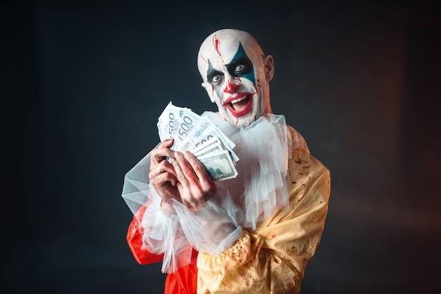 Enge bloedige clown met gekke ogen houdt fan van geld. man met make-up in carnavalskostuum, gekke maniak