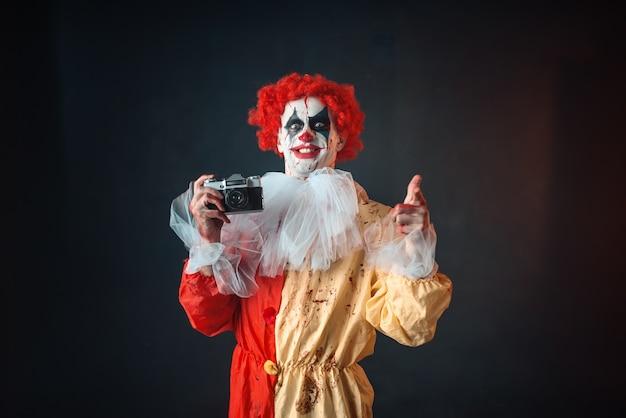 Enge bloedige clown met gekke ogen maakt foto