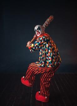 Enge bloedige clown reikt honkbalknuppel uit