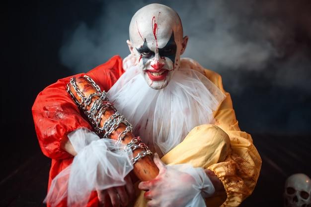 Enge bloedige clown, verspreide delen van het menselijk lichaam