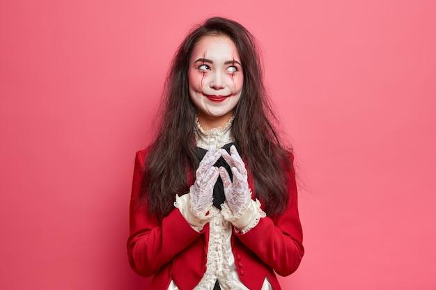 Enge brunette vrouw met zombie-ogen en bloedige littekens gekleed in halloween-kostuum steekt vingers en heeft een kwaad plan geïsoleerd over roze muur