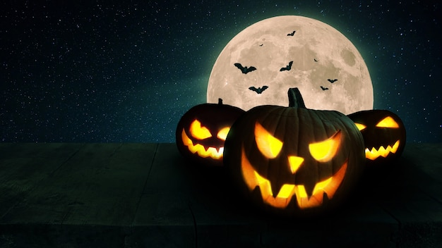 Enge gloeiende pompoenen met lampjes op een houten tafel met een volle maan en vleermuizen. halloween behang en achtergrond. vrije ruimte voor ontwerp en tekst