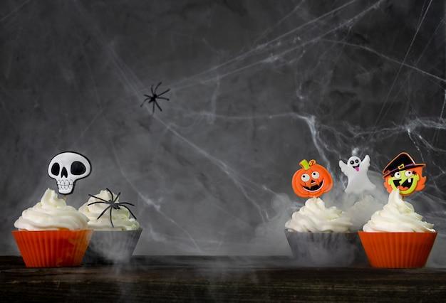 Enge halloween cupcakes op een donkere achtergrond met spinnenwebben en rook.