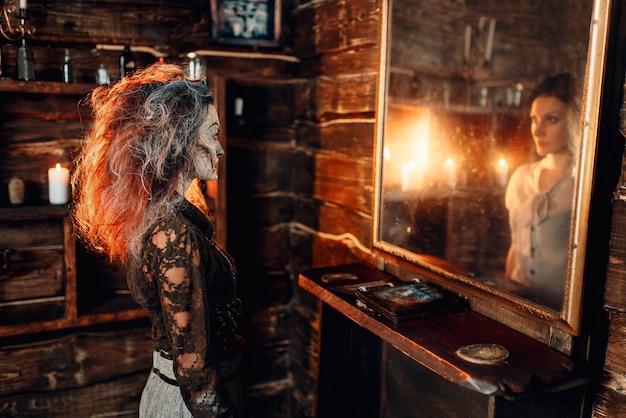 Enge heks voor de spiegel wordt een jonge schattige vrouw in de reflectie, spirituele seance. vrouwelijke voorspeller roept de geesten