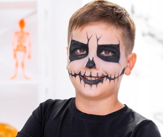 Enge jonge die jongen met gezicht voor halloween wordt geschilderd