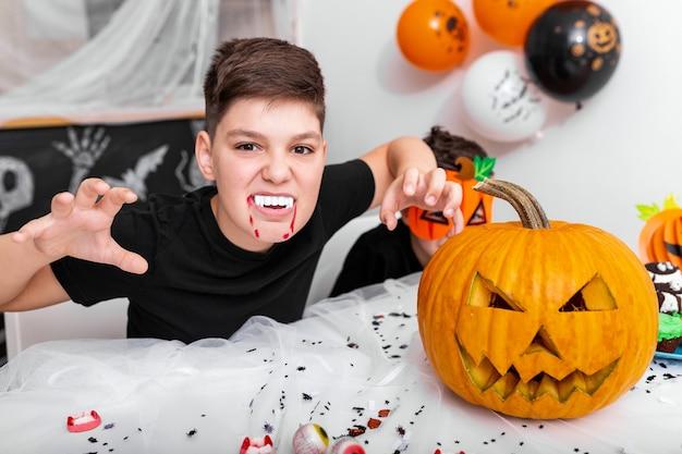 Enge jongen met hoektanden op het halloween-feest. jack o 'lantern halloween-pompoen op tafel