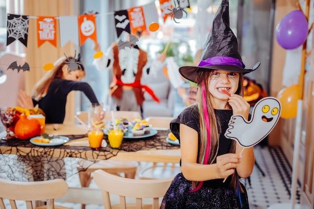 Enge partij. donkerharige mooi schattig meisje draagt tovenaarshoed opgewonden bijwonen van enge halloween-feest