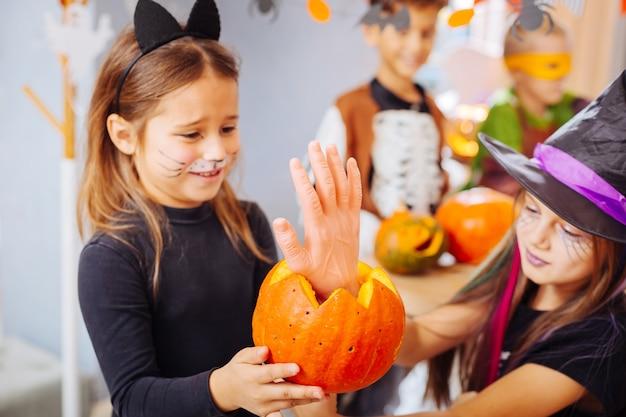 Enge snoepjes. twee mooie donkerharige meisjes die geweldige halloween-kostuums dragen en enge snoepjes eten