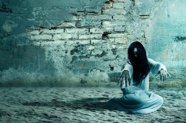Enge spookvrouw die met een gebarsten muur kruipt