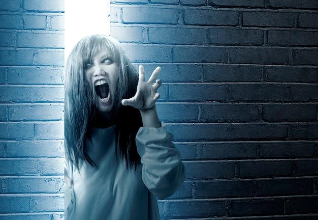 Enge spookvrouw die zich achter de bakstenen muur met heldere achtergrond bevindt