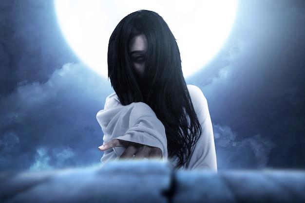 Enge spookvrouw die zich met de achtergrond van de nachtscène bevindt. halloween-concept