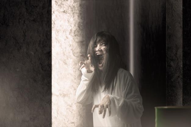 Enge spookvrouw met bloed en boos gezicht met klauwende handen achtervolgde het verlaten gebouw