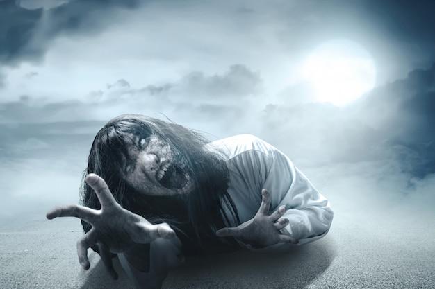 Enge spookvrouw met bloed en boos gezicht met klauwende handen die in het donker kruipen