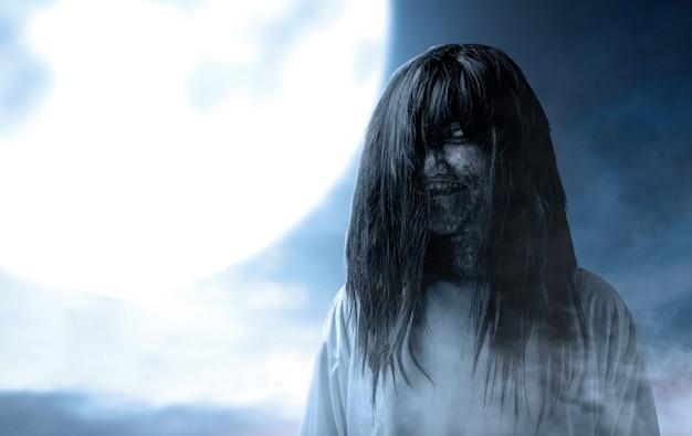 Enge spookvrouw met bloed en vuil gezicht die zich met maanlichtachtergrond bevinden