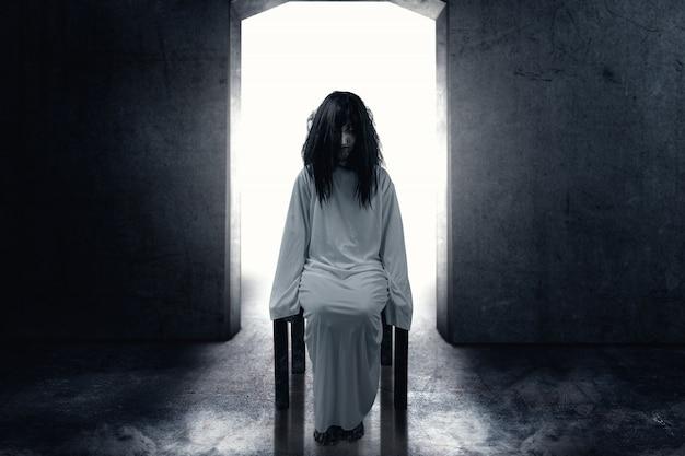 Enge spookvrouw met bloed en vuile gezichtszitting in de donkere ruimte