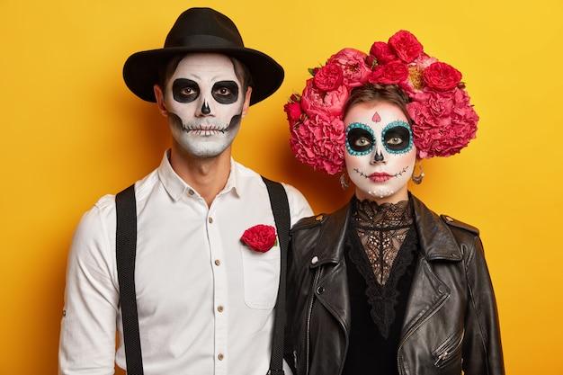 Enge vrouw, man draagt creatieve schedelmake-up, leren zwarte jas, hoed, pioenrozenkrans, bereid je voor op halloween-carnaval of verkleedfeest