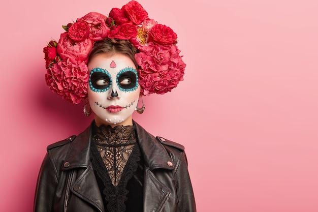 Enge vrouw met schedelmake-up, bereidt zich voor op day of dead in mexico