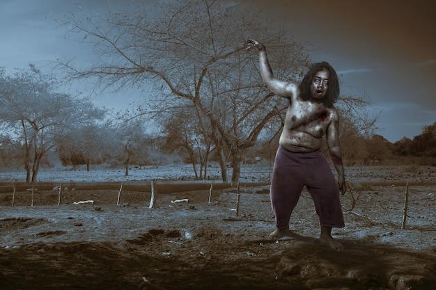 Enge zombie met bloed en wond aan zijn lichaam die op het veld loopt