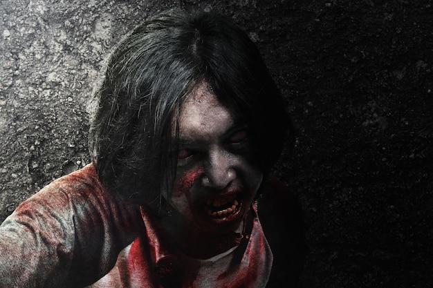 Enge zombie met bloed en wond op zijn lichaam kruipend met grunge muur achtergrond