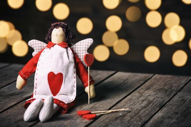 Engel een zacht stuk speelgoed met hartzitting op oude houten achtergrond. valentine concept