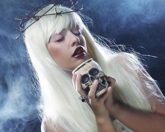 Engelachtige lange haarvrouw met schedel