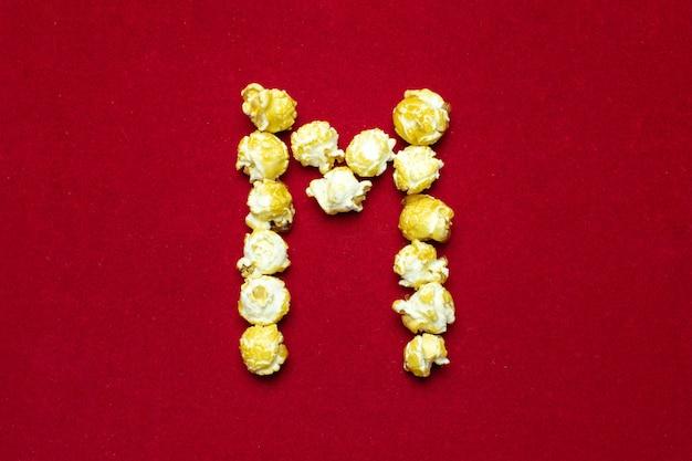 Engels alfabet van bioscooppopcorn. letter m. rode achtergrond voor ontwerp