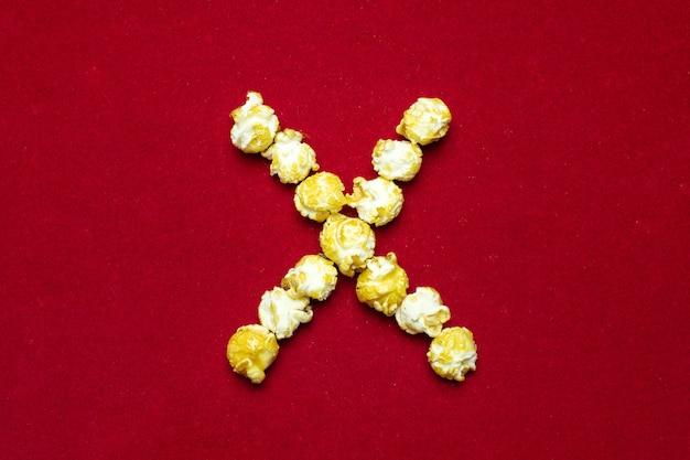 Engels alfabet van bioscooppopcorn. letter x. rode achtergrond voor ontwerp