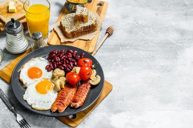 Engels ontbijt. diverse snacks met sinaasappelsap. op een rustieke tafel.
