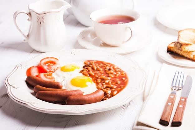 Engels ontbijt - eieren, worstjes met bonen en thee met melk