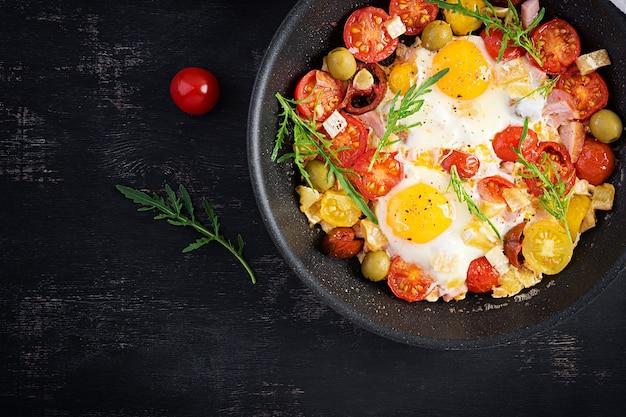 Engels ontbijt - gebakken eieren, ham, tomaten en rucola. amerikaans eten. bovenaanzicht, overhead, kopieerruimte