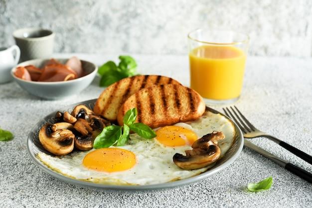 Engels ontbijt. gebakken eieren met champignons en ham met een glas sinaasappelsap als ontbijt. goedemorgen.