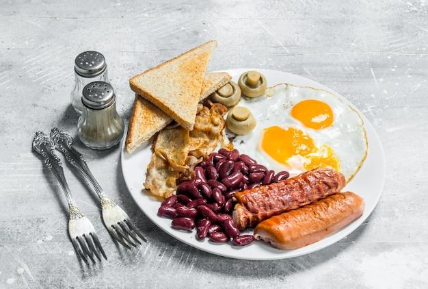 Engels ontbijt. gebakken eieren met worst, spek en bonen. op een rustieke ondergrond.