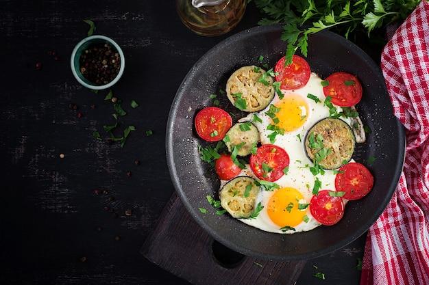 Engels ontbijt - gebakken eieren, tomaten en aubergine. amerikaans eten. bovenaanzicht, overhead, kopieerruimte