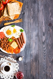 Engels ontbijt, gebakken eieren, worstjes, bonen, brood toast, tomaten, kaas op een houten tafel,