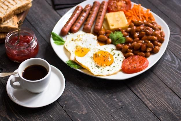 Engels ontbijt. gebakken eieren, worstjes, bonen, brood toast, tomaten, kaas,