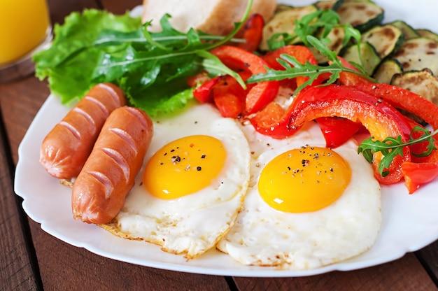 Engels ontbijt - gebakken eieren, worstjes, courgette en paprika