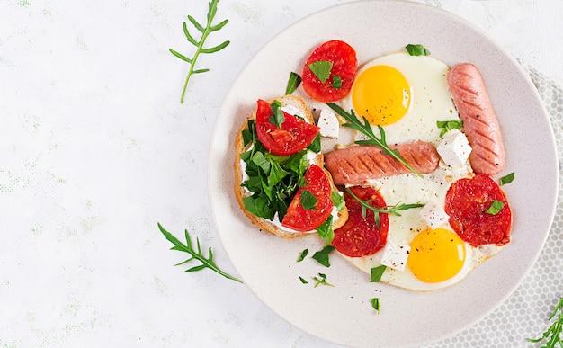 Engels ontbijt - gebakken eieren, worstjes, tomaten en fetakaas. amerikaans eten. bovenaanzicht, overhead, kopieerruimte