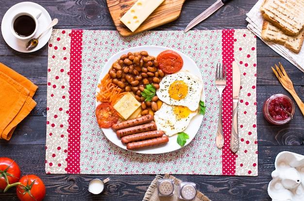 Engels ontbijt. gebraden eieren worstjes brood brood toast tomaten kaas op een houten achtergrond