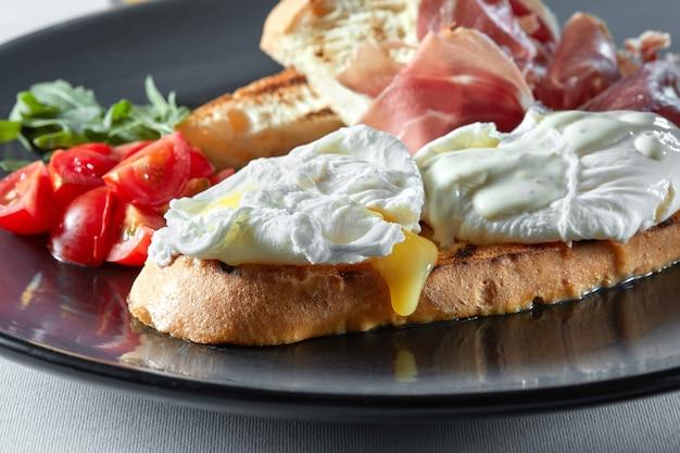 Engels ontbijt met benedictus-eieren, toast, tomaten, sinaasappelsap en spek