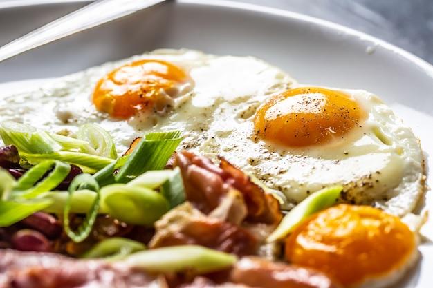 Engels ontbijt met eieren, spek, bonen en iyoung-ui in witte plaat.