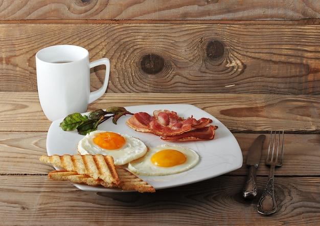 Engels ontbijt met roerei, spek, gebakken toast en thee