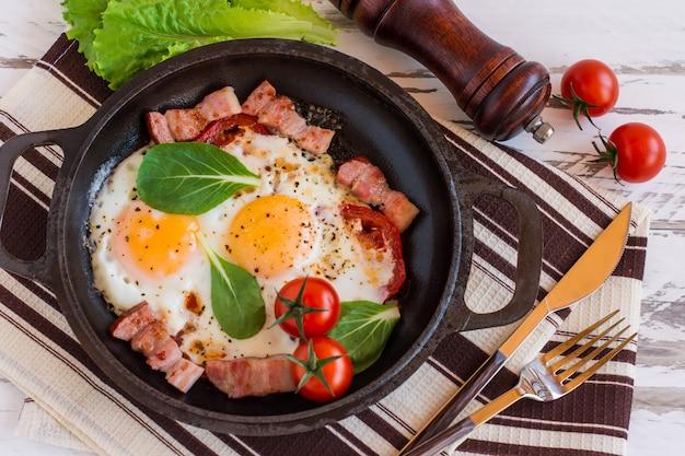 Engels ontbijt of lunch met gebakken ei, spinazie, rucola, tomaten en spek op zwarte pan.